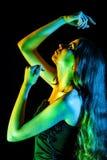 Schöne junge Frau in den grünen, blauen und gelben Lichtern Stockfotografie