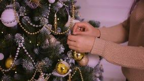 Schöne junge Frau in der beige Strickjacke verzierte Baum stock video