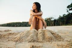 Schöne junge Frau der Beine begraben im Sand auf Strand Reizvolle Frau, die auf Sand sitzt Stockbild
