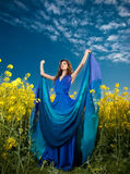 Schöne junge Frau in der blauen Kleideraufstellung im Freien mit bewölktem drastischem Himmel im Hintergrund Stockfotografie