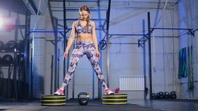 Schöne junge Frau in der grauen Sportkleidung Begins Übung tuend mit Gewicht Kreuzsitz stock video
