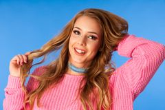 Schöne junge Frau in der rosa Strickjacke und im Jeansrock über vibrierendem blauem Hintergrund lizenzfreie stockfotografie