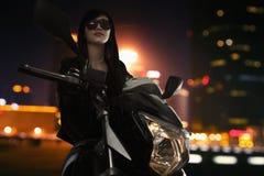 Schöne junge Frau in der Sonnenbrille, die in der Nacht auf einem Motorrad in Peking sitzt Lizenzfreie Stockfotos