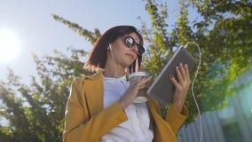 Schöne junge Frau in der Sonnenbrille, die heißen Kaffee in der Schale während sie eine Mitteilung auf Tablet-Computer sendend hä stock video