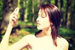 Schöne junge Frau in der Spitze unter Verwendung des Sprays Stockbilder