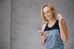 Schöne junge Frau in der Sportkleidung und in den Kopfhörern hört Musik unter Verwendung eines Smartphone Lizenzfreie Stockfotografie