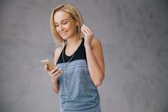 Schöne junge Frau in der Sportkleidung und in den Kopfhörern hört Musik unter Verwendung eines Smartphone Stockfoto