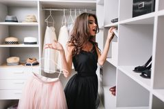 Schöne junge Frau in der stilvollen Garderobe, die Kasten mit den Schuhen untersucht, interessiert, was inner ist, rosa flaumiges stockfoto