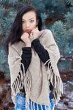 Schöne junge Frau in der Strickjacke und in Jeans, die Wald im Winter nahe Bäumen einfrieren Lizenzfreie Stockfotos
