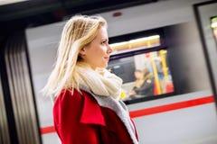 Schöne junge Frau an der Untertageplattform, wartend Lizenzfreie Stockfotografie