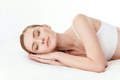Schöne junge Frau in der weißen Unterwäsche, die mit geschlossenen Augen liegt Stockbilder