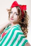 Schöne junge Frau des Pinupmädchens mit den roten Lippen und ein Bogen auf ihrem Kopf, der das Kameranahaufnahme-Porträtbild betr Stockbild