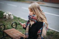 Schöne junge Frau des Porträts auf Bank im städtischen Hintergrund, der Telefon schaut stockbilder