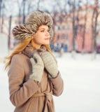 Schöne junge Frau des Porträts, die einen Mantel und einen Hut trägt stockfotos