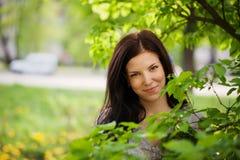 Schöne junge Frau des Porträts in einem Garten Lizenzfreie Stockfotos