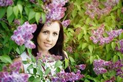 Schöne junge Frau des Porträts nahe der blühenden Flieder Stockbild