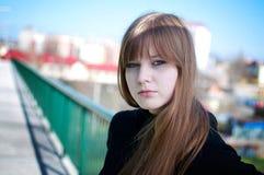 Schöne junge Frau, die über der Stadtansicht aufwirft stockfotografie
