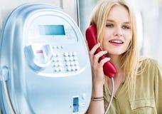 Schöne junge Frau, die über ein allgemeines Münztelefon spricht Glücklicher Ausdruck stockfoto