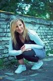Schöne junge Frau, die über Graffitiwand aufwirft lizenzfreie stockbilder
