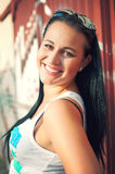 Schöne junge Frau, die über roter Wand aufwirft lizenzfreie stockfotografie