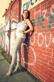 Schöne junge Frau, die über roter Wand aufwirft lizenzfreie stockfotos