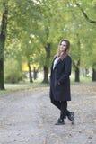 Schöne junge Frau, die allein in den Park geht Stockbild