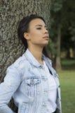 Schöne junge Frau, die allein in den Park geht Lizenzfreies Stockfoto
