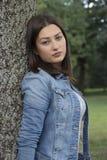 Schöne junge Frau, die allein in den Park geht Stockfotografie