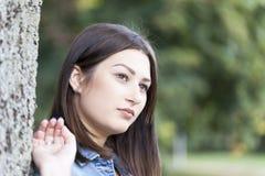 Schöne junge Frau, die allein in den Park geht Stockbilder