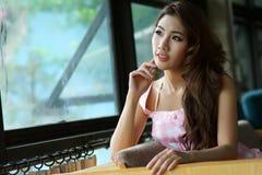 Schöne junge Frau, die allein im Café aufwirft Stockfotografie