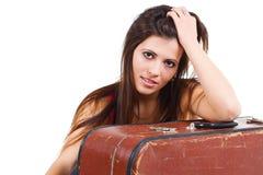 Schöne junge Frau, die auf altem Koffer sich lehnt Stockfoto
