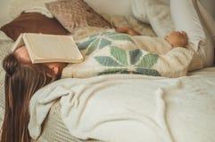 Schöne junge Frau, die auf Bett mit dem Buch bedeckt ihr Gesicht weil Ablesenbuch mit dem Vorbereiten der Prüfung des Colleges sc stockbild