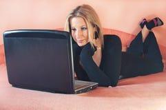 Schöne junge Frau, die auf Bett mit Laptop liegt stockbild