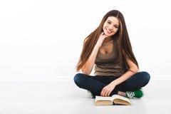 Schöne junge Frau, die auf Boden sitzt stockfotos
