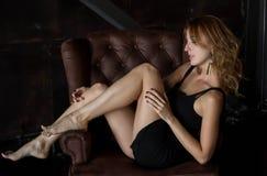 Schöne junge Frau, die auf Couch aufwirft Lizenzfreie Stockfotografie