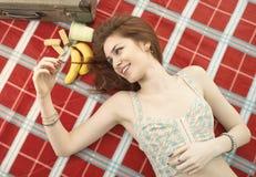 Schöne junge Frau, die auf Decke sich entspannt Stockbilder