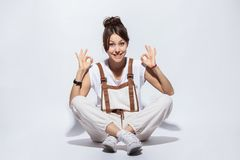 Schöne junge Frau, die auf dem Boden, dem lächelnden Positiv, okayzeichen mit der Hand und den Fingern tuend sitzt Erfolgreicher  stockfotos