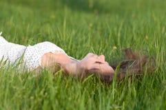 Schöne junge Frau, die auf dem grünen Gras liegt Lizenzfreies Stockbild
