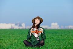 Schöne junge Frau, die auf dem Gras mit Geschenk auf dem wond sitzt stockfotos