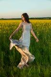 Schöne junge Frau, die auf dem rapseed Gebiet aufwirft Stockfotos