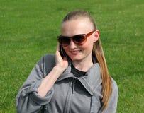 Schöne junge Frau, die auf dem Rasen sitzt Lizenzfreie Stockfotografie