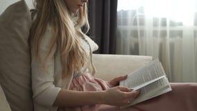 Schöne junge Frau, die auf dem Sofalesebuch und -c$lächeln sitzt stock video