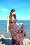 Schöne junge Frau, die auf dem Stein auf der Küste steht Stockfotos
