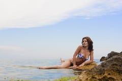 Schöne junge Frau, die auf dem Stein sitzt Stockbilder