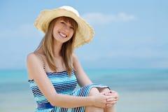 Schöne junge Frau, die auf dem Strand lächelt Lizenzfreie Stockfotos