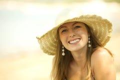 Schöne junge Frau, die auf dem Strand lächelt lizenzfreie stockfotografie