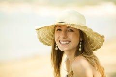 Schöne junge Frau, die auf dem Strand lächelt lizenzfreies stockfoto