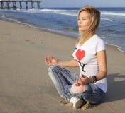 Schöne junge Frau, die auf dem Strand meditiert Lizenzfreie Stockfotografie