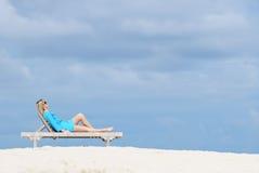 Schöne junge Frau, die auf dem Strand sich entspannt Lizenzfreie Stockfotografie