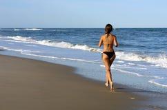 Schöne junge Frau, die auf den Strand läuft Stockfotografie